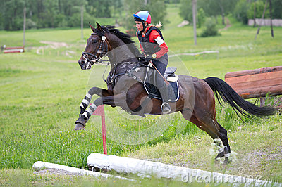 Woman eventer on horse is jump the open ditch Editorial Stock Photo