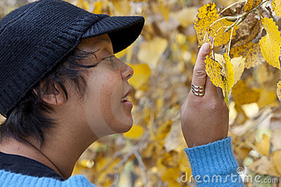 Woman examining autumn leaves