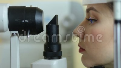 Woman examining eyesight in ophthalmology clinic stock video
