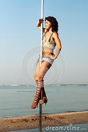 Woman exercise pole dance against sea landscape.