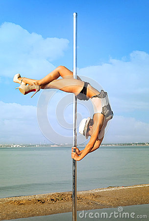 Woman exercise pole dance against sea landscape.