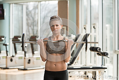 Woman Exercising Biceps With Barbell In Gym