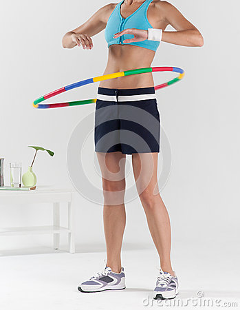 Woman exercising with colorful plastic hula hoop