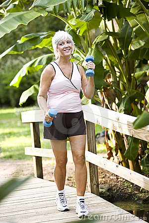 Woman exercising in park walking with hand weights