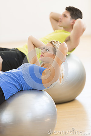 Woman Exercising On Pilate With Man In Background At Club