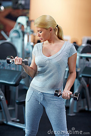 Woman exercising with two dumbbells