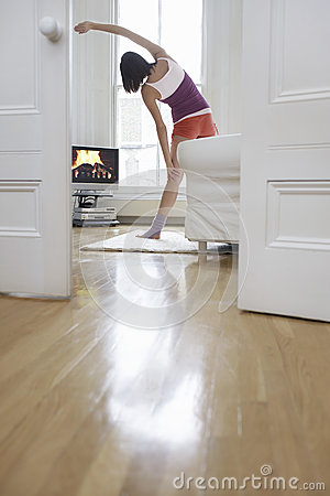 Woman Exercising And Watching Television At Home