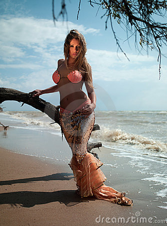 Woman in exotic dress standing on the beach