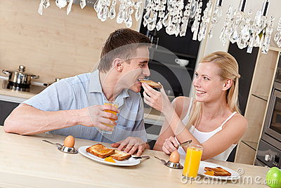 Woman feeds his husband with breakfast in the kitchen