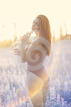 Woman in field with flower at summer sunset.