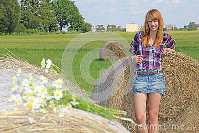 Woman in a field with hay bales