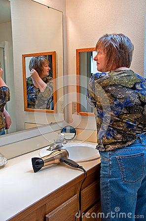 Woman Fixing Her Hair In Bathroom Mirror