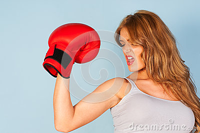 Woman flexing arm muscles wearing a boxing glove