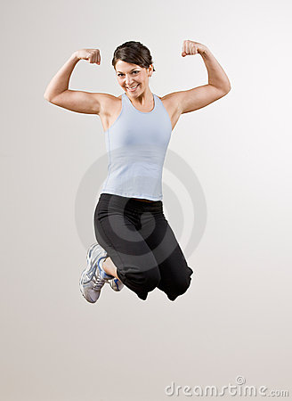 Woman flexing biceps while jumping in mid-air
