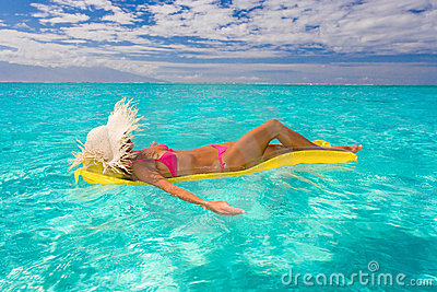woman floating on raft in tropical water