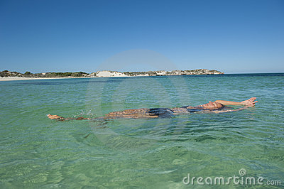 Woman floating and relaxing in ocean