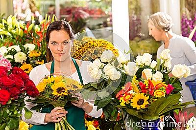 Woman florist selling sunflowers bouquet flower shop