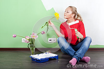 Woman with flower and paint roller in hands