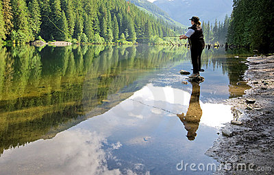 Woman fly fishing at a lake