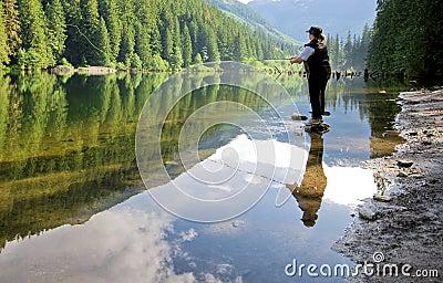 Woman fly fishing at a lake