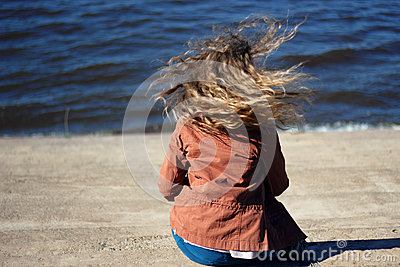 Woman with flying blonde curly hair on sea background