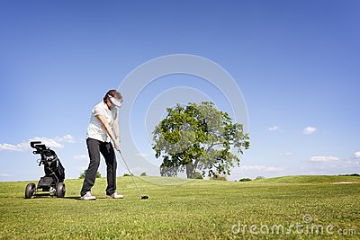 Woman focusing on golf fairway.
