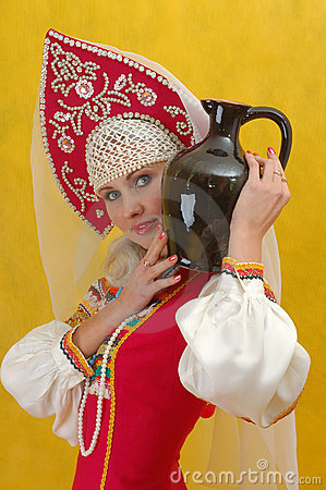 Woman in a folk russian dress holds a jug