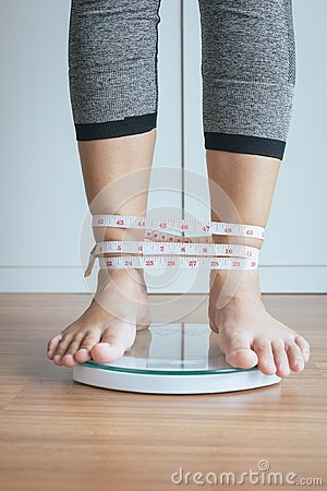 Free Woman Foot Standing On Electronic Weigh Scales With Tape Measure Leg Winded Stock Images - 123347844