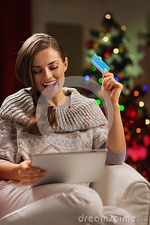 Woman in front of Christmas tree with tablet PC
