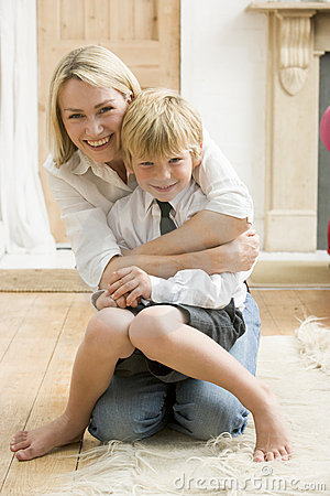 Woman in front hallway hugging young boy and smili