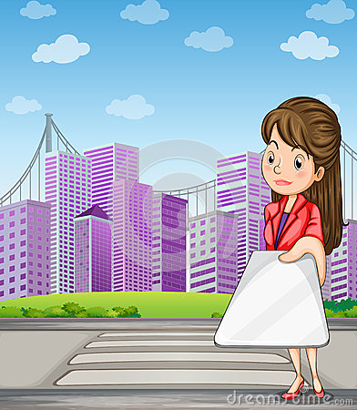 A woman in front of the tall buildings holding a gadget