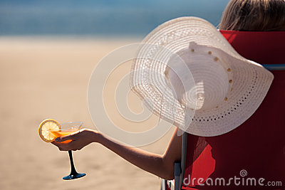 Woman with a fruit cocktail on a tropical beach