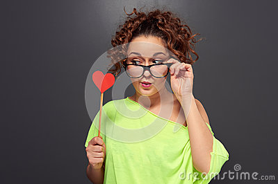 Woman in funny glasses looking at red heart