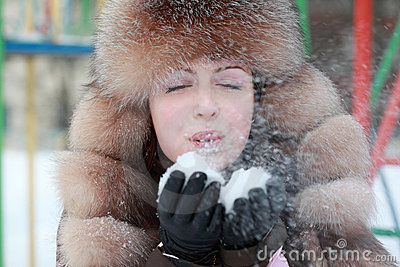 Woman in fur hat blowing snowflakes in winter