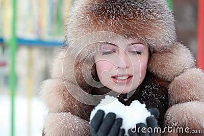 Woman in fur hat keeps snow in winter
