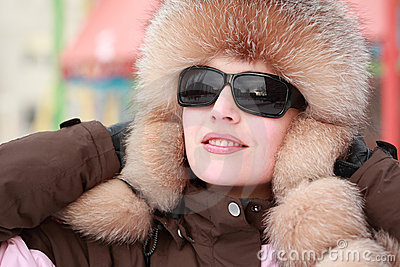 Woman in fur hat and sunglasses in winter
