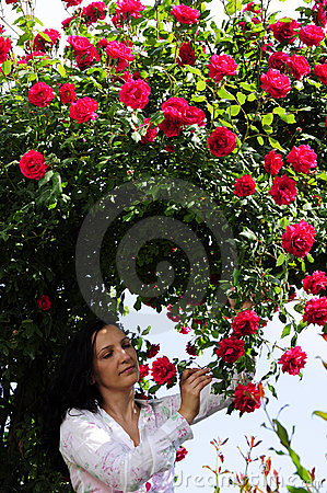 Woman in garden under red roses bower
