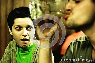 Woman gawking at man drinking
