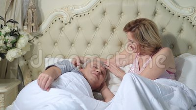 Woman gently waking up man in the morning stock video footage