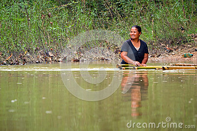 Woman getting across the river in Thailand Editorial Image