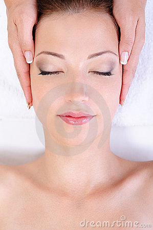 Woman getting face massage in spa salon