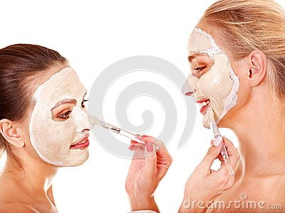 Woman getting facial mask.