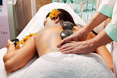 Woman getting a hot stone massage in spa salon