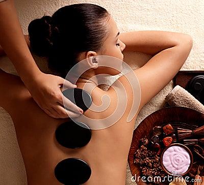 Woman getting hot stone massage in spa salon.