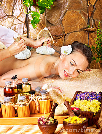 Woman getting thai herbal compress massage .