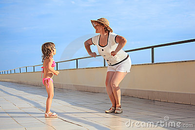 Woman And Girl Do Morning Exercise On Veranda Stock Photos - Image: 13021233