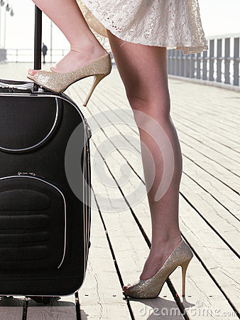 Woman girl foot sea mooring suitcase on a pier