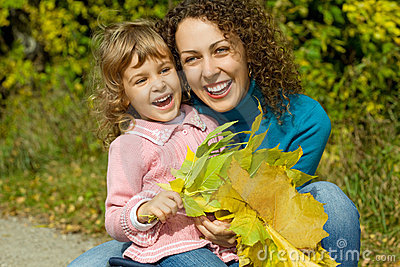 Woman and girl laugh with leaves in garden