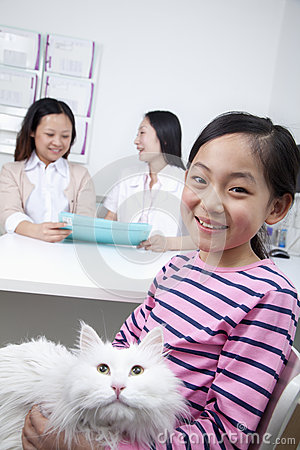 Woman and girl with pet dog in veterinarian s office