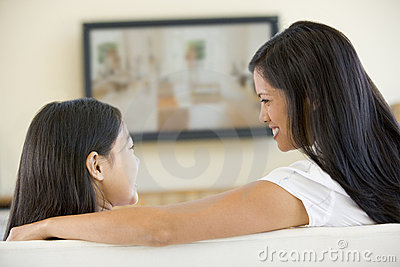 Woman and girl in room with flat screen television